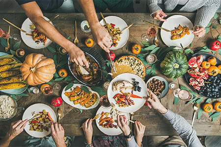 friends pass savory dishes over a Thanksgiving table