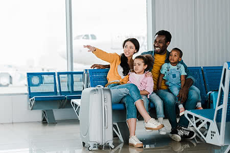 a family sits in an airport waiting for a flight
